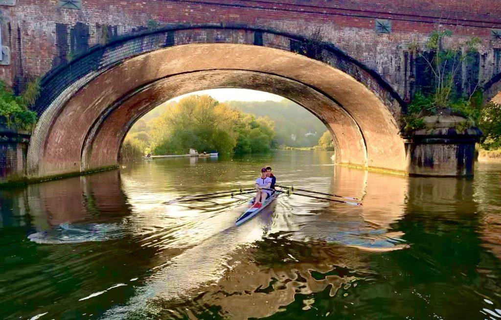 A Pangbourne School double scull rowing through Gatehampton bridge.